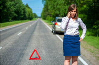 Picture of Girl in skirt on side of the road on her phone with car in background