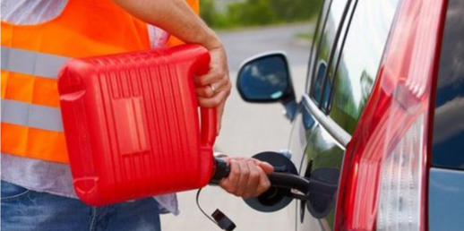 Picture of Guy filling up car with jerry can on side of the road