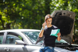 Picture of Guy leaning on car with hood open holding paper while on the phone