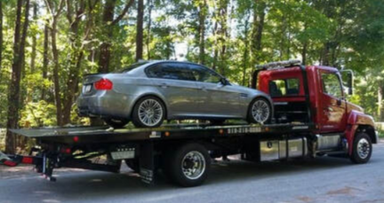Picture of Silver Car on Flat Bed Tow Truck Driving through forested road